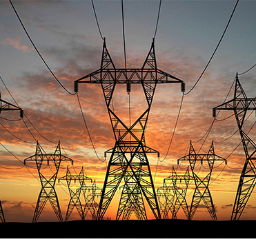 Electricity pilons in field in sunset