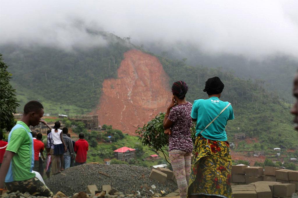 Civilians look on at landscape devastated by floods and landslides in Sierra Leone