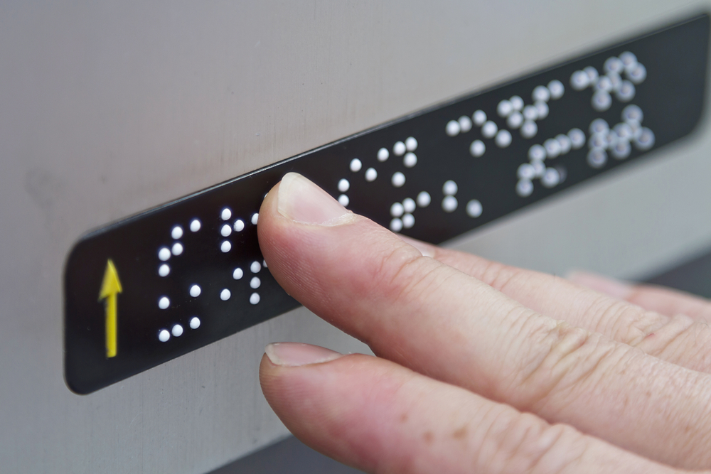 Blind person reading braille note on ATM