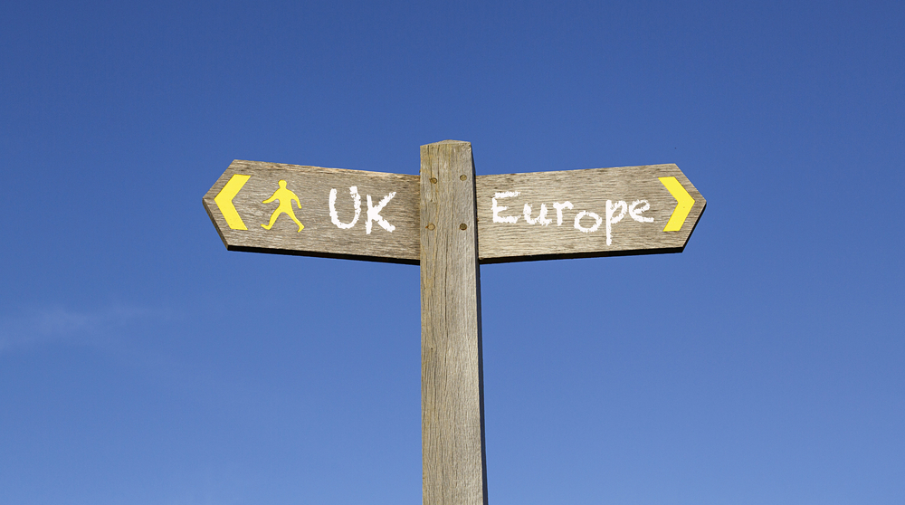 Signposts point in opposite directions to UK and Europe