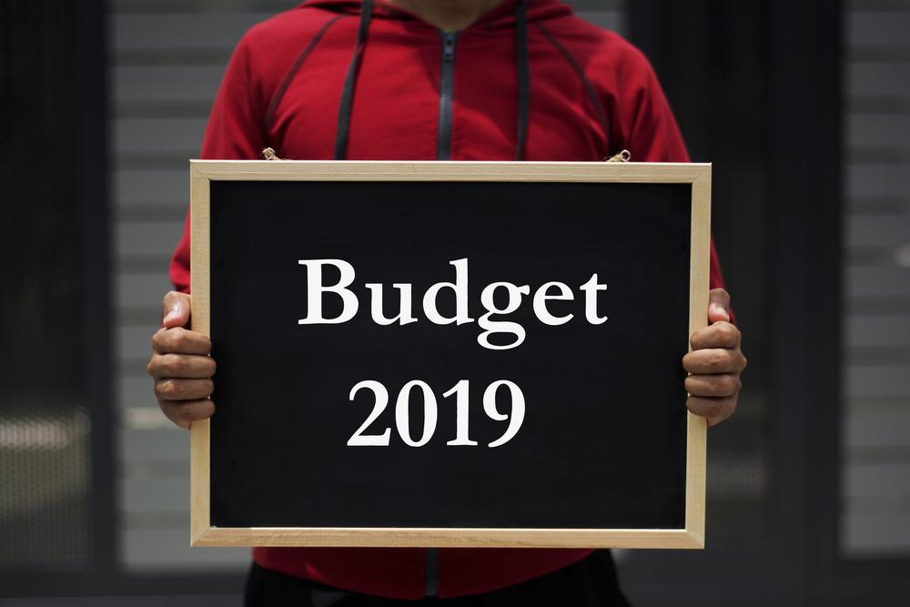 Person holding blackboard saying Budget 2019