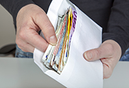 man holding envelope with lots of cash