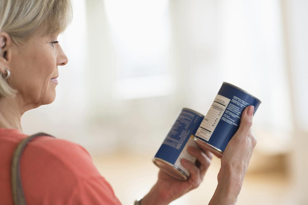 Lady holding 2 tins of food looking at labels