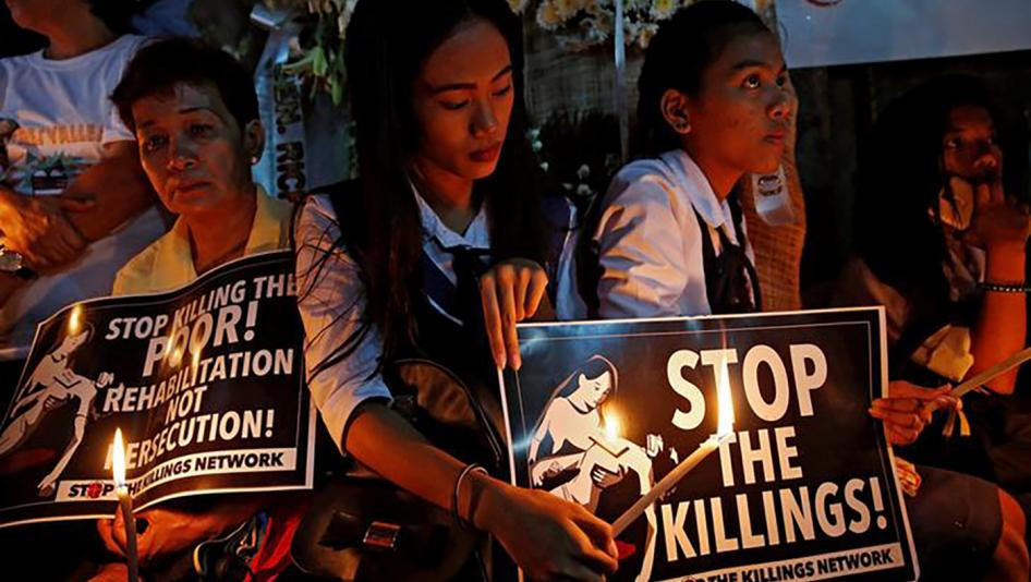 Filipino people holding signs says stop the killings
