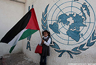 Palestinian girl in front of UNRWA logo holding palestinian flag